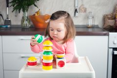 Construction a 2 year old girl with long hair plays with a designer at home, builds towers, rejoices at successes royalty free stock photography