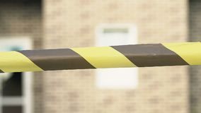 Construction yellow-black tape front of building, warning sign, danger risk. Stock footage stock video footage