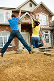 Construction: Young Couple Jumps in Excitement royalty free stock images