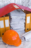 Constructional objects. Yellow, red file folders, helmet and heap of design drawings are on the table. Business still-life Royalty Free Stock Images