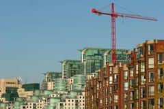 Constructions en verre et de brique avec la grue rouge Photo stock
