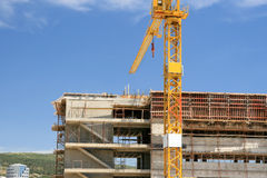 Constructions site. Building under construction, with a yellow crane in front of the building Stock Photo