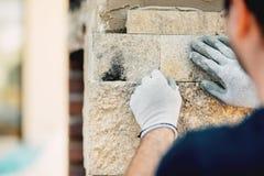 Constructionworker som installerar yttersida för stenvägg med cement för att renovera för hus royaltyfria bilder
