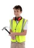 Constructor adolescente joven del aprendiz que sostiene el martillo Foto de archivo libre de regalías