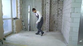 Constructor atlético feliz que hace trucos en el emplazamiento de la obra almacen de metraje de vídeo