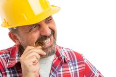 Constructor biting bitcoin. Male constructor checking golden bitcoin by biting it as greedy concept isolated on white background stock image