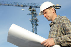 Constructor with blueprints. Constructor in hardhat with blueprints against modern crane Stock Photos
