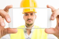 Constructor or builder taking a selfie with smartphone. Back hd camera confident and isolated on white background Royalty Free Stock Images