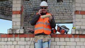 Constructor con el rodillo de pintura que habla en el teléfono elegante metrajes