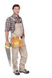 Constructor con la sierra de la mano. Imagen de archivo