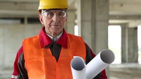 Constructor con los dibujos del edificio en el sitio del proyecto almacen de video