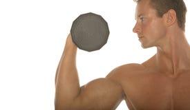 Constructor de carrocería atractivo muscular que se resuelve con pesa de gimnasia Imagen de archivo libre de regalías