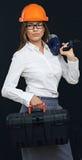 Constructor de la mujer con las herramientas de la caja que celebran el taladro en hombro fotos de archivo libres de regalías