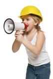 Constructor de la niña en casco amarillo que grita en el altavoz Foto de archivo