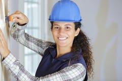Constructor de sexo femenino que usa el raspador del papel pintado imagen de archivo