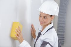 Constructor de sexo femenino que usa la esponja en la pared enyesada fotografía de archivo