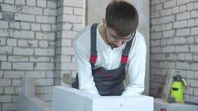 Constructor de sexo masculino joven que comprueba uniformidad del muro de cemento aireado metrajes