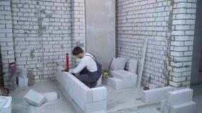 Constructor de sexo masculino que pone el bloque de cemento aireado y que lo comprueba con el nivel de burbuja de aire almacen de metraje de vídeo