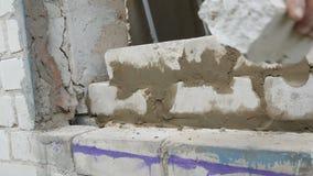 Constructor de sexo masculino que pone el ladrillo blanco en el cemento y que coloca la pared Manos del hombre que ponen los ladr metrajes
