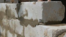 Constructor de sexo masculino que pone el ladrillo blanco en el cemento y que coloca la pared Manos del hombre que ponen los ladr almacen de video