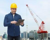 Constructor de sexo masculino sonriente en casco con PC de la tableta Fotos de archivo libres de regalías