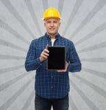Constructor de sexo masculino sonriente en casco con PC de la tableta Imagenes de archivo