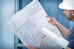 Constructor del arquitecto que estudia el plan de la disposición de los cuartos Imágenes de archivo libres de regalías