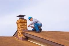 Constructor del contratista en el tejado con la chimenea azul del calafateo del casco de protección imagen de archivo