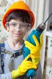 Constructor del muchacho en gafas y con un taladro imagen de archivo