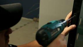 Constructor, en casquillo negro, base de los partes movibles del castillo en puerta Destornillador de las aplicaciones almacen de metraje de vídeo