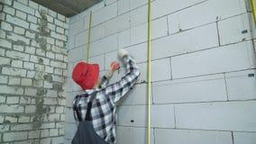 Constructor en desgaste del trabajo y abrazaderas rojas de la construcción de los partes movibles del casquillo en la pared del b almacen de metraje de vídeo