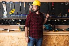 d3a5ad0af8d Constructor en el casco de protección que sostiene el martillo en looki del  hombro cuidadosamente foto
