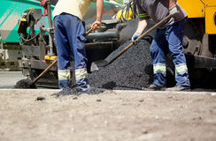 Constructor en la máquina de asfaltado de la pavimentadora durante la reparación de la calle del camino Fotografía de archivo libre de regalías
