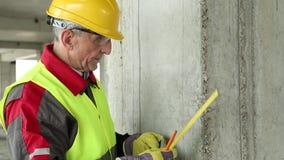Constructor en ropa de funcionamiento y amarillo difícilmente en emplazamiento de la obra metrajes