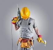 Constructor en un casco con un martillo y un taladro Imágenes de archivo libres de regalías