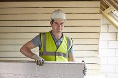 Constructor Fitting Insulation Boards al tejado de la nueva casa Imágenes de archivo libres de regalías