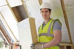 Constructor Fitting Insulation Boards en el tejado de la nueva casa Fotografía de archivo libre de regalías