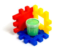 Constructor and jar of gouache. Children's multicolored constructor on which stands the green jar with gouache isolated on white background Royalty Free Stock Photo