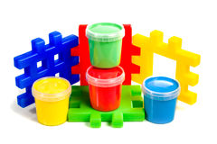 Constructor and jars of paint. On the bright a colorful children's constructor are four jars of paint isolated on white background Royalty Free Stock Image