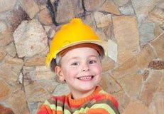 Constructor joven con una pared de piedra del fondo Imagen de archivo