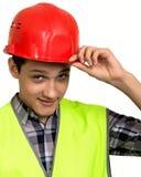 Constructor joven en chaleco y casco en un fondo blanco Fotografía de archivo libre de regalías