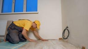 Constructor joven que pone el entarimado en el nuevo apartamento imágenes de archivo libres de regalías