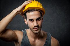 Constructor Portrait. Photo of male constructor with helmet over grey rural background Royalty Free Stock Photo