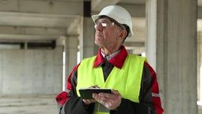 Constructor principal con la tableta en el emplazamiento de la obra almacen de video