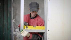 Constructor profesional usando el indicador de nivelación para medir en solar metrajes