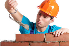 Constructor with putty knife building wall. Constructor with putty knife building a brick wall Stock Photography