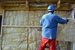 Constructor que aísla la casa de madera con lanas minerales Foto de archivo