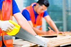 Constructor que asierra un tablero de madera de emplazamiento del edificio o de la obra Imagen de archivo