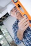 Constructor que comprueba el trabajo usando nivel de alcohol foto de archivo