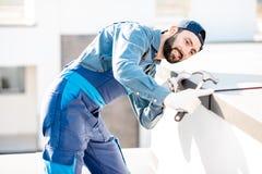 Constructor que monta la cubierta del metal en el parapeto de un nuevo edificio fotos de archivo